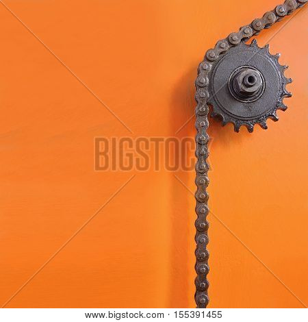 Metal cogwheel and chain on orange background with empty space for text.