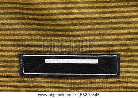 Blank clothes label on striped yellow cloth as a background