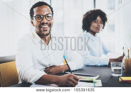 Two young african business people working together in a modern office.Black man and woman smiling at the camera.Horizontal, blurred