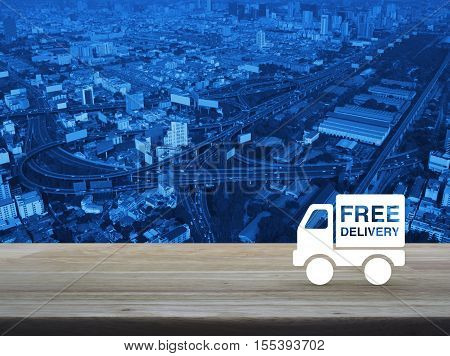Free delivery truck icon on wooden table over aerial of modern city tower street and expressway Transportation business concept