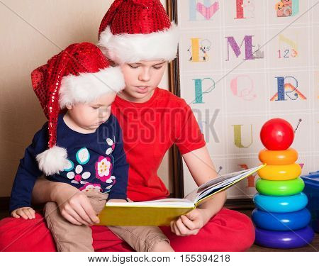 Children in Santa hats reading a Christmas book. Big brother reading to his little baby sister in the nursery.