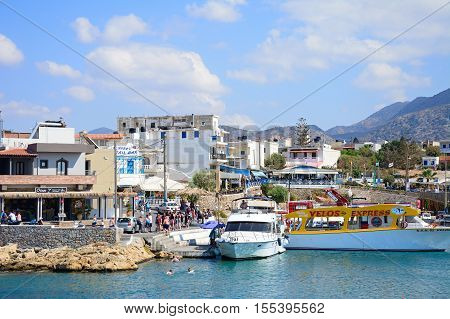 SISSI, CRETE - SEPTEMBER 14, 2016 - Boats moored in the harbour with waterfront restaurants to the rear and tourists enjoying the setting Sissi Crete Europe, September 14, 2016.