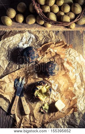 Jacket potatoes with salt and butter on old wooden table