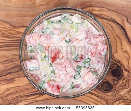 Organic tomato and green onion scallion salad with sour cream in bowl on olive wood cutting board