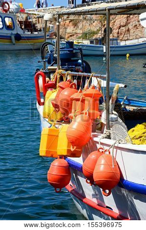 SISSI, CRETE - SEPTEMBER 14, 2016 - Orange and yellow fishing floats on the back of a Traditional Greek fishing boat moored in the harbour Sissi Crete Greece Europe, September 14, 2016.