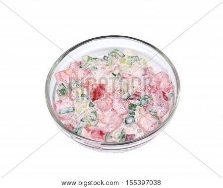 Organic tomato and green onion scallion salad with sour cream in bowl isolated on white background