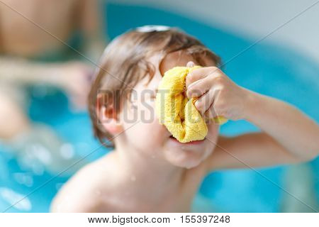 Cute little child taking bath in bathtub at home. Angry sad kid boy having fear by washing hair and splashing with soap.