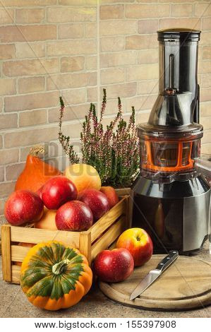 Juicer and apple juice. Preparing healthy fresh juices. Home juicing apples in the kitchen. Processing autumnal fruit.