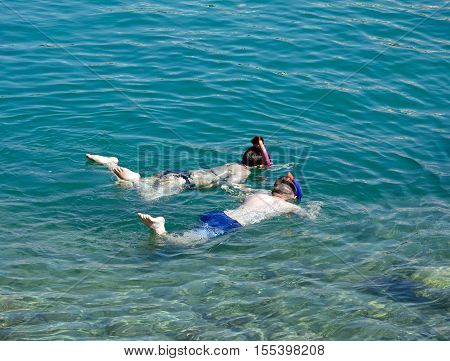 Children snorkelling in shallow water in the bay Sissi Crete Europe.