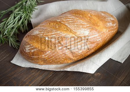 Homemade bread with crust on a dark wooden table. Fresh loaf of wheat bread.