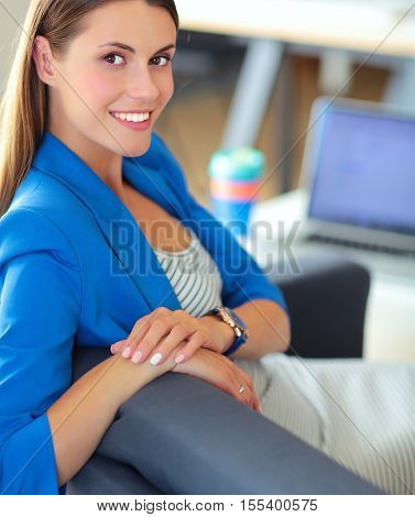 Young beautiful businesswoman sitting on the sofa