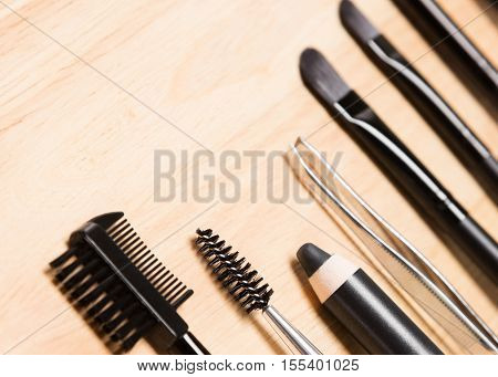 Accessories for care of the brows: brow comb / brush combo, spoolie brush, eyebrow pencil, tweezers, angled brushes on wood background. Eyebrow grooming tools. Shallow depth of field. Copy space
