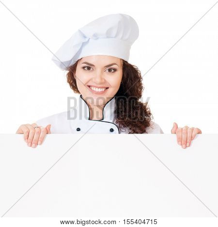 Woman cook or baker looking over paper sign billboard. Caucasian girl wearing chef hat, isolated on white background. Advertisement and food concept - smiling female chef with white blank board.