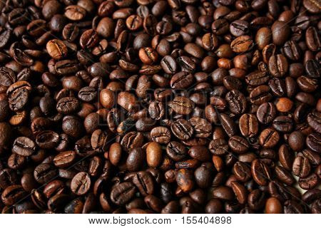 Background of ripe brown coffee beans that lie in one promiscuous heap.