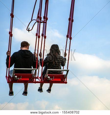 People having fun In swing carousel against blue sky