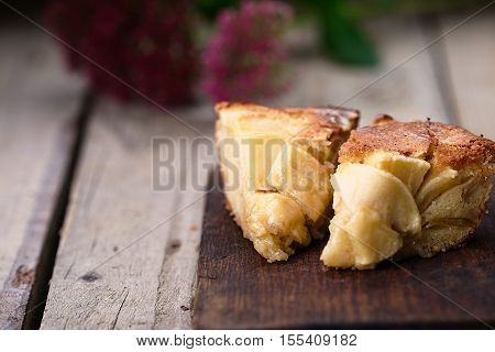 Slice of a french apple cake with vanilla and rum on a cutting board. Wooden background. Horizontal