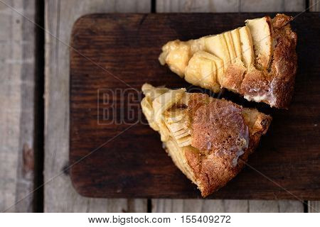 Slice of a french apple cake with vanilla and rum on a cutting board. Wooden background
