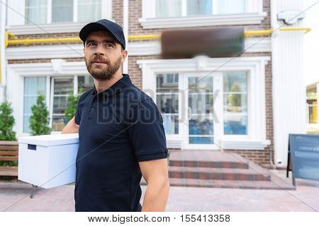 man holding a package in front of the house and looking into a camera