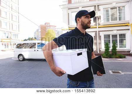 young carrier in baseball hat walking with a white package
