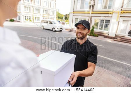 bearded delivery man standing with box in front of a customer, selective focus