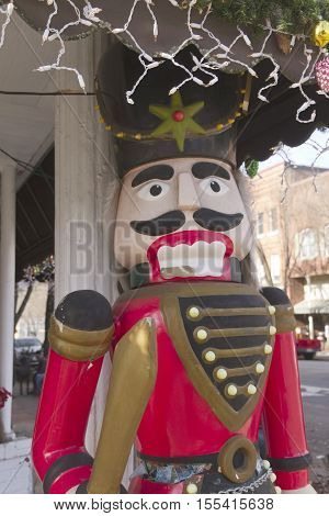 Brevard North Carolina USA - December 11 2015: A life-sized wooden Christmas toy soldier stands outside of a store under some Christmas lights and decorations in downtown Brevard North Carolina during the holidays