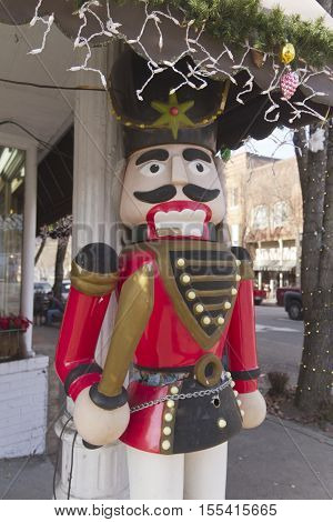 Brevard North Carolina USA - December 11 2015: A life-sized wooden Christmas toy soldier stands outside of a store under some Christmas lights and decorations in Brevard North Carolina during the holidays