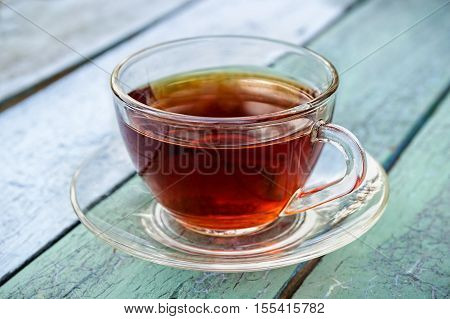 Glass cup of tea on old green blue wooden surface.