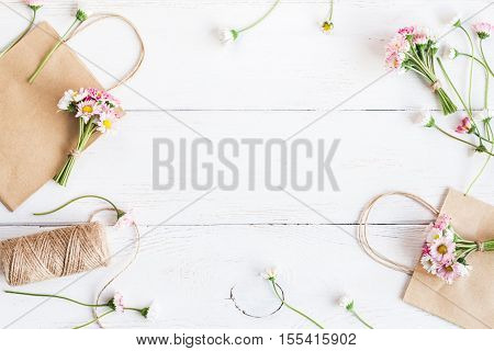 Workspace with small bouquets of daisy flowers paper bags. Creation. Top view flat lay poster