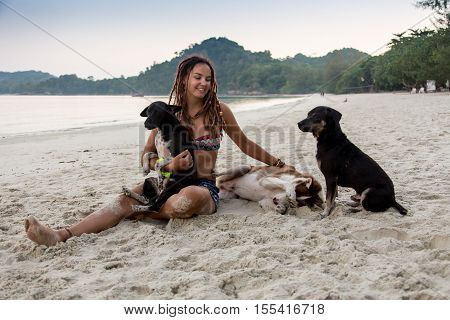 Cheerful pretty young woman in hat sitting and hugging her dog on the beach.