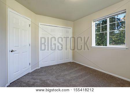 White Doors Closet And A Window In Empty Beige Room
