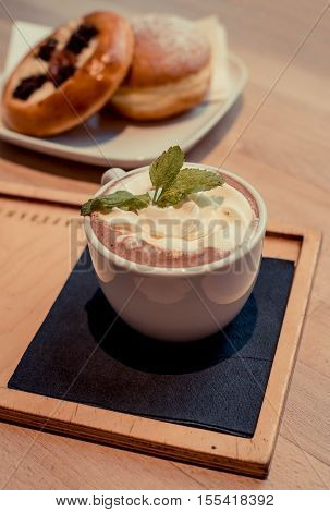 Hot chocolate with bread mint on top vintage photo in coffee shop