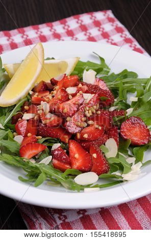 Salad of arugula and strawberries with crushed peanuts almonds