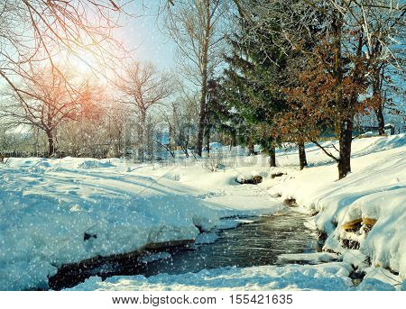 Winter rural landscape in sunny weather- winter village with stream and winter snowdrifts on the foreground. Sunny view of picturesque winter nature. Rural winter landscape under snowfall and sunshine