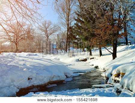 Winter landscape in sunny weather- winter view of rural houses with stream and winter snowdrifts on the foreground. Sunny view of picturesque winter nature. Rural winter landscape under sunshine