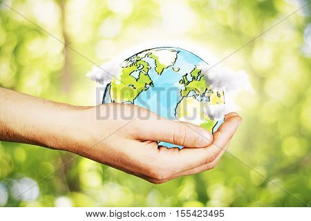 Hand holding creative drawn terrestrial globe with clouds on blurry green background. Eco concept