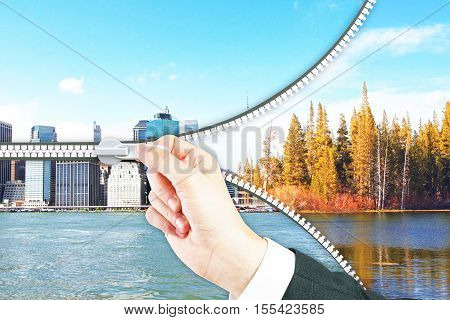 Abstract image of hand zipping landscape into city. Urbanization concept