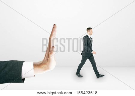 Tiny businessman walking away from huge human palm on light background