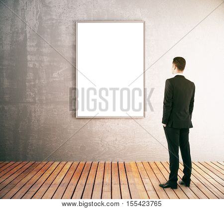 Back view of businessman looking at blank picture frame in interior with concrete wall and wooden floor. Mock up 3D Rendering