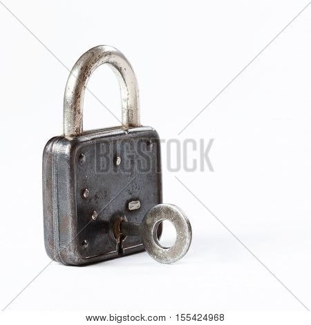 Vintage padlock with key in hole. hanging lock close-up. texture and detailed.