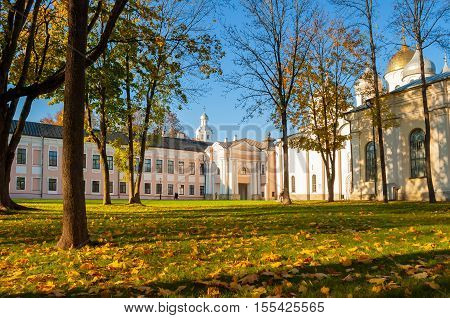 Veliky Novgorod Kremlin park with Clock Tower of St Sophia Cathedral and fallen autumn leaves on the foreground in Novgorod Russia. Focus at the clock tower. Architecture autumn sunny landscape