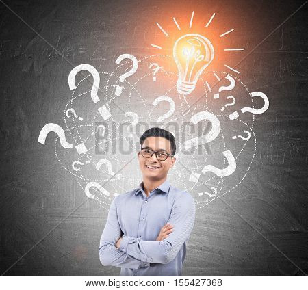 Portrait of Asian man wearing glasses and standing near chalkboard with multiple question marks and light bulb. Concept of answer finding