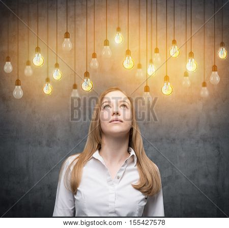 Blonde woman is looking upwards at many light bulbs hanging on their cords. Concept of an idea
