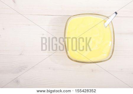 Little bowl of vanilla custard on wooden background