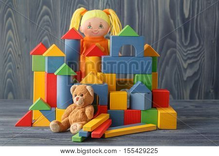 Toy house and doll with blocks on wooden table