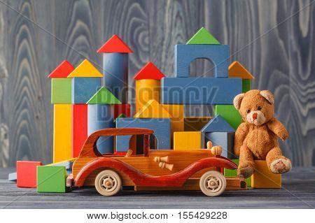 House Made Of Wooden Blocks To Assemble, Near A Toy And A Wooden Toy Car