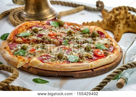 Closeup Of Pizza On A Boat Made Of Salami And Olives