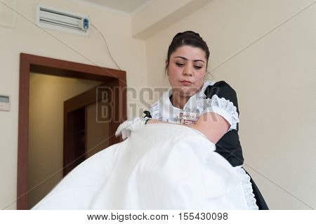 MOSCOW - OCTOBER 31: Maid girl dressed in black putting on duvet cover on duvet at room in Izmaylovo hotel on October 31 2016 in Moscow. Izmailovo Hotel is four-building hotel located in Izmaylovo District of Moscow.