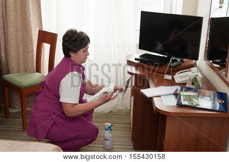 MOSCOW - OCTOBER 31: Maid woman dressed in purple making cleaning procedure at room in Izmaylovo hotel on October 31 2016 in Moscow. Izmailovo Hotel is four-building hotel located in Izmaylovo District of Moscow.