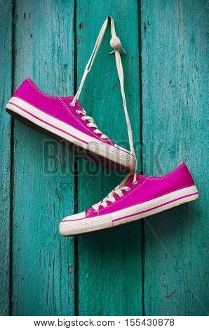 pair of bright pink sneakers hanging on a cord on a nail wooden turquoise background old
