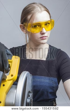 young beautiful woman in overalls and glasses with disk saw preparing for cutting. close-up portrait.